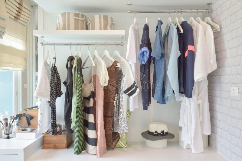 Tissus de la jeunesse accrochant dans la garde-robe ouverte dans la chambre à coucher photo stock