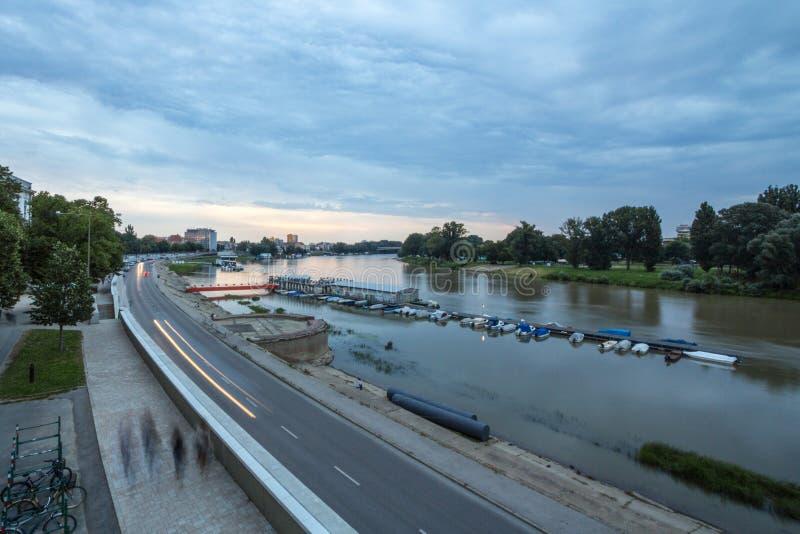 Tisza flodbanker i det Szeged centret som ses in i ljuset under solnedgång under en molnig sommareftermiddag arkivbild