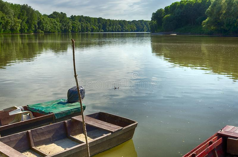 Tisza River at Tiszadada, Hungary. Summer season landscape. Wooden boats on the water. Green forest along the river. stock photography