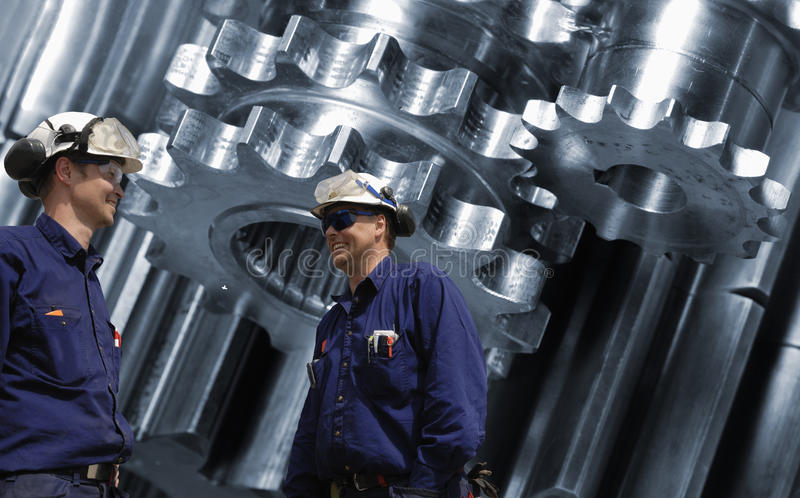 Titanium aerospace engineering parts. Titanium and steel aerospace parts, gears and cogwheels, two engineers talking in the foreground stock images