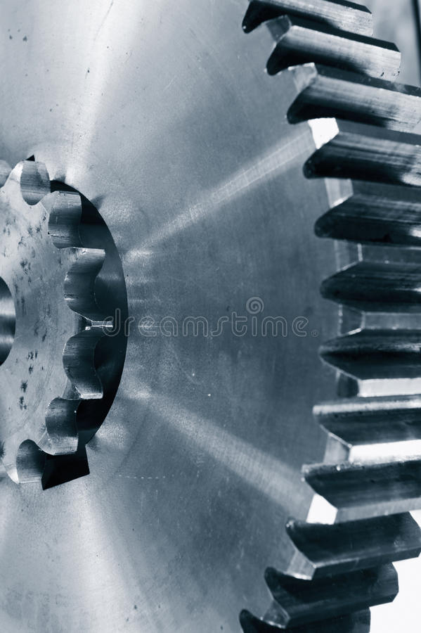 Titanium and steel gear wheels. Large and small power gears, titanium and steel. aerospace parts. blue toning concept, close-ups stock image