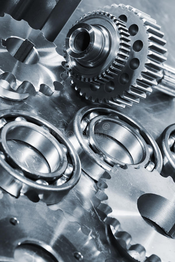 Titanium and steel gears and ball-bearings. Industrial gears and bearings against titanium background, blue metal toning idea royalty free stock photos