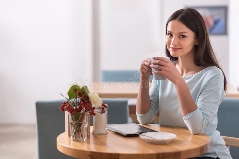 Titel: Lycklig charmig härlig kvinna som kopplar av i en coffee shop royaltyfria bilder