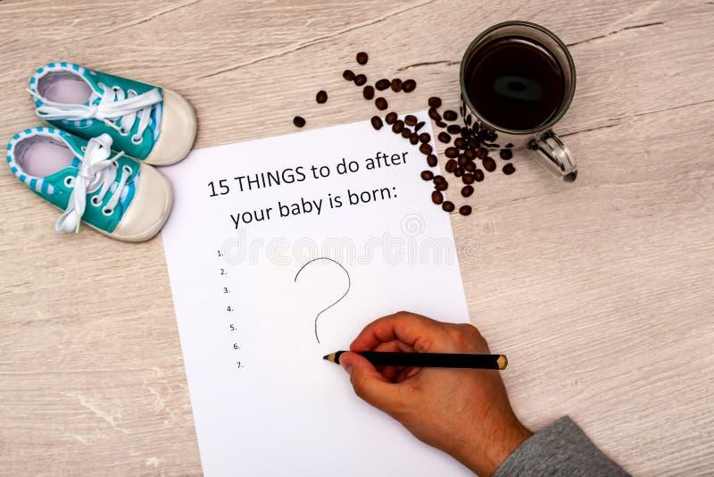 Titel vijftien dingen na uw baby te doen is geboren Wit blad op een houten achtergrond met een vraagteken, babybuiten royalty-vrije stock foto's