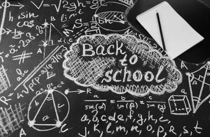 Titel zurück zu Schule, Formeln geschrieben durch weiße Kreide auf die schwarze Schultafel und Notizbuch mit Bleistift lizenzfreie stockfotos