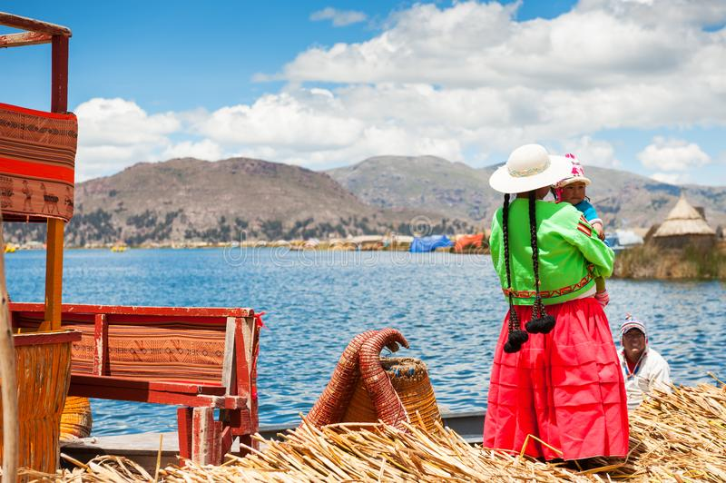 Local people on Uros floating islands on Titicaca lake in Peru royalty free stock photography