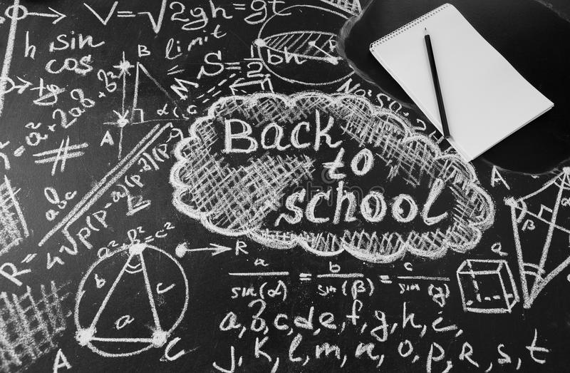 Title Back to school, formulas written by white chalk on the black school chalkboard and notebook with pencil royalty free stock photos