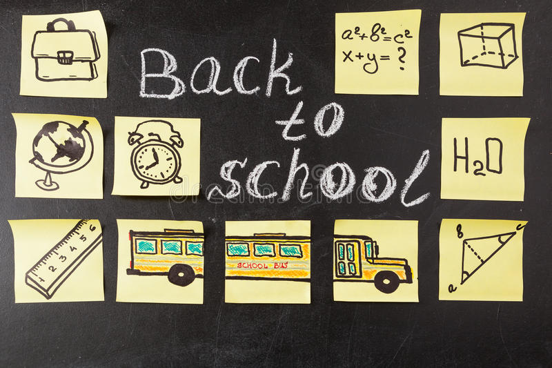 Title Back to school written by chalk and images of school bus and attributes written on the pieces of paper. Back to school background with title Back to school stock photos