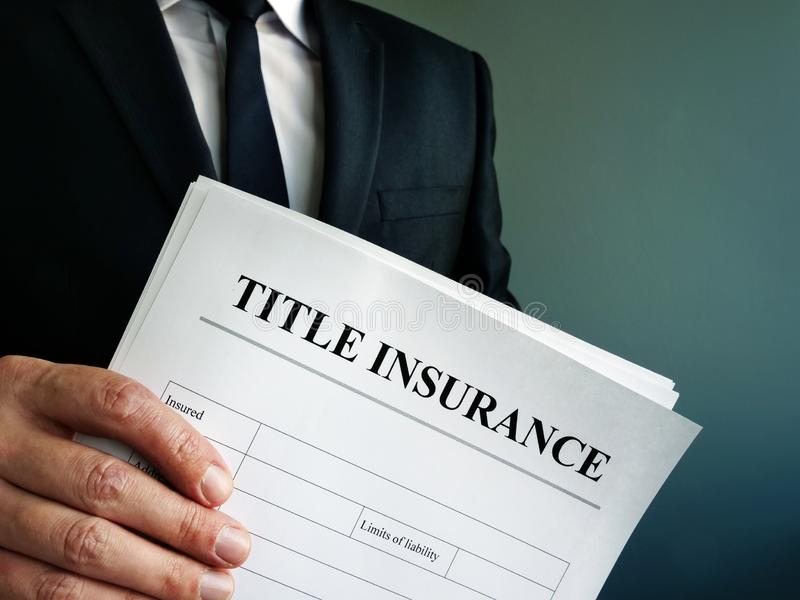 Title Insurance agreement in the hand of a businessman royalty free stock photo