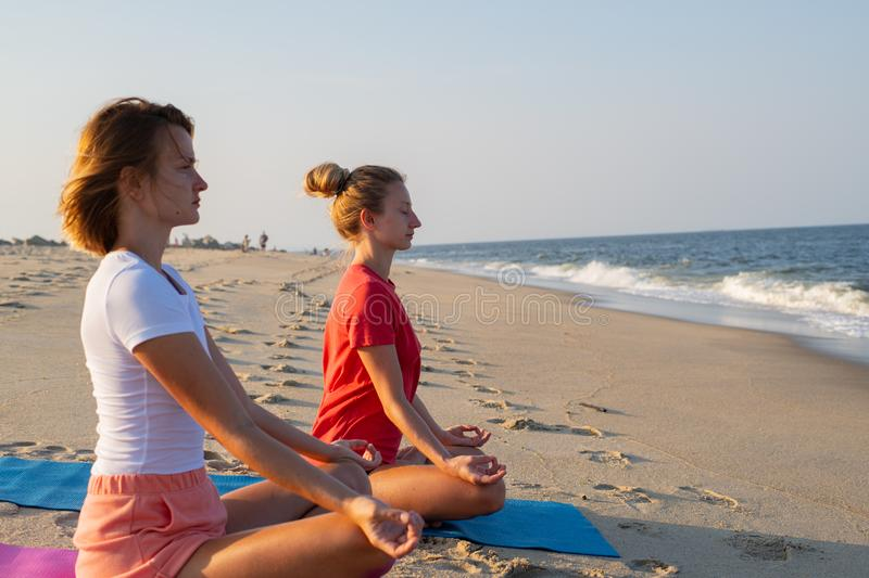 Young women practicing yoga on the beach at sunset. Girls meditating, sitting in lotus pose royalty free stock photography