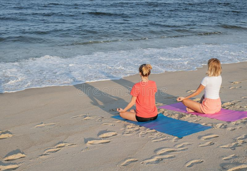 Young women practicing yoga on the beach at sunset. Girls meditating, sitting in lotus pose stock image