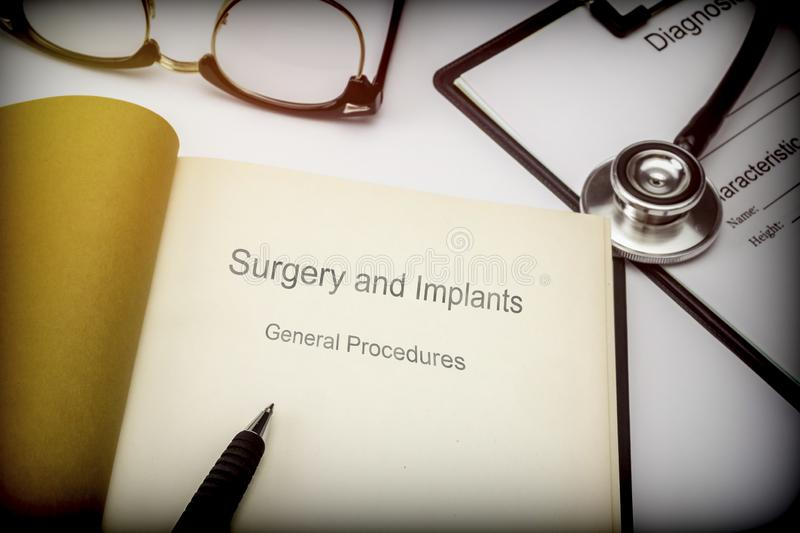 Titled book Surgery and implants general procedures along with medical equipment. Conceptual image stock photography