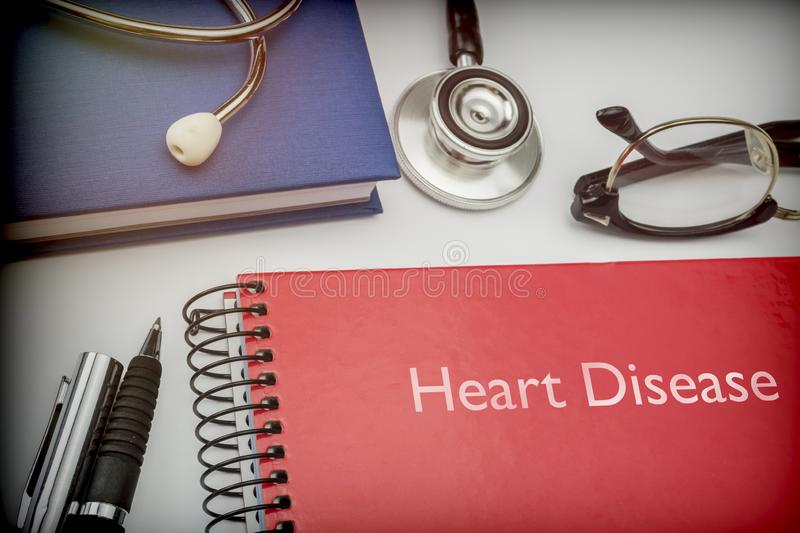 Titled red book Heart Disease along with medical equipment. Conceptual image stock photo