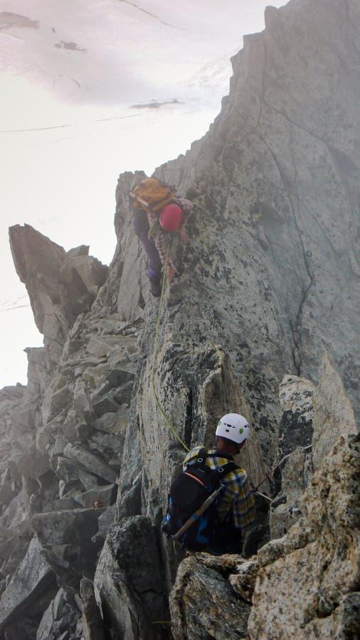 Titre de guide et de client de montagne vers un haut sommet alpin un jour brumeux photos stock
