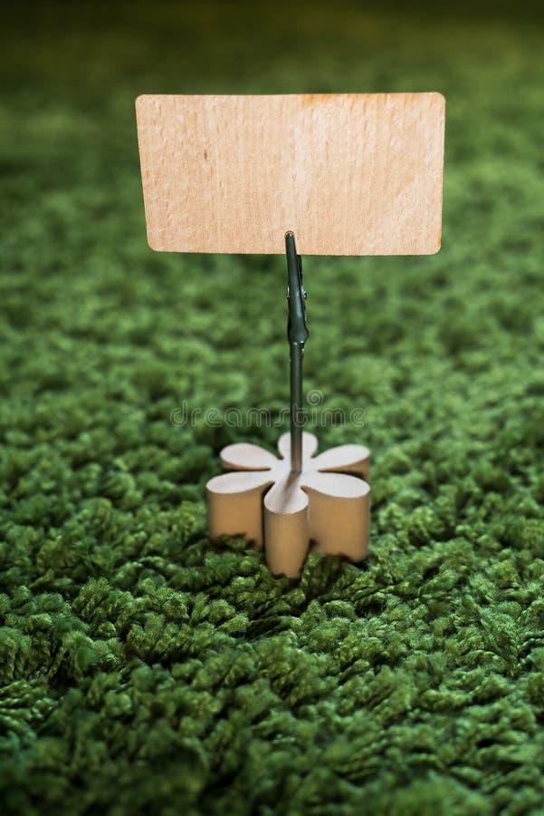 Titular do cartão do grampo com a flor de madeira no holdin do tapete da grama verde fotografia de stock royalty free