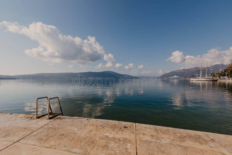 TIVAT, MONTENEGRO - 9 DE NOVEMBRO DE 2018: Turistas que andam na frente mar?tima ensolarada da cidade de Tivat fotografia de stock