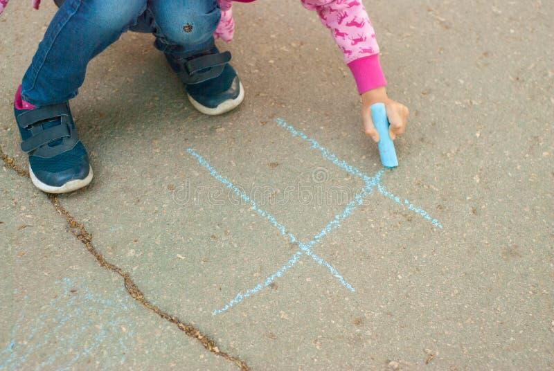 Tiza caucásica agradable del drenaje de la niña en la actividad del Parenting de Asphalt Lines Blue Chalk Educative para los niño fotografía de archivo