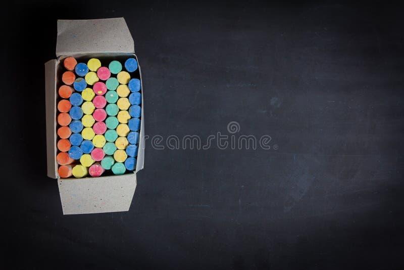 Tiza coloreada en un fondo de la pizarra foto de archivo libre de regalías