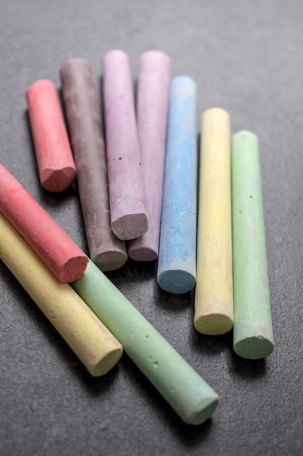 Tiza coloreada en un fondo de la pizarra fotos de archivo libres de regalías