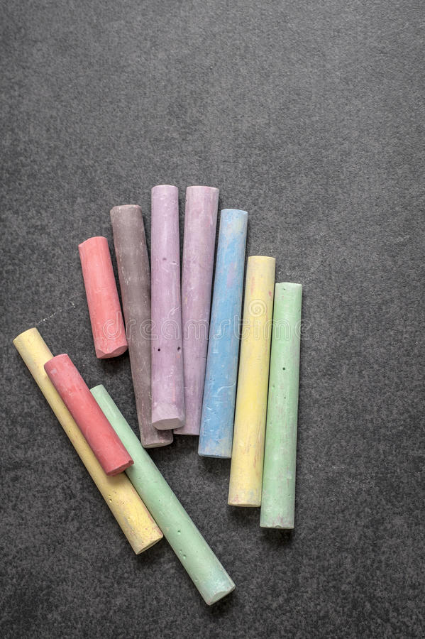 Tiza coloreada en un fondo de la pizarra imagen de archivo