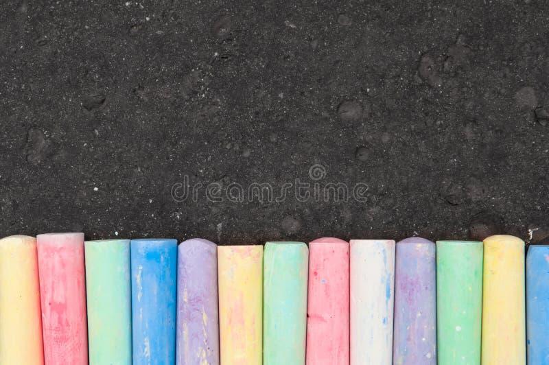 Tiza en colores pastel colorida de la acera en fondo oscuro del asfalto foto de archivo libre de regalías