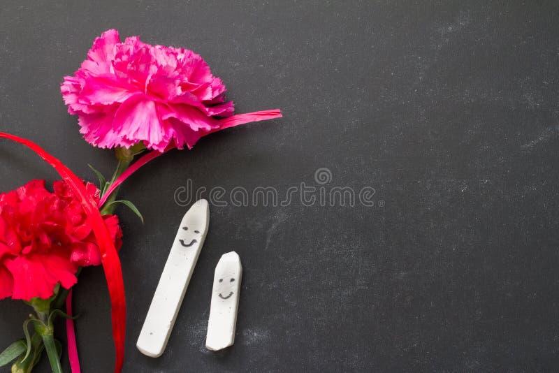 Tiza feliz en la pizarra con el fondo del extracto del día del profesor de las flores fotografía de archivo libre de regalías