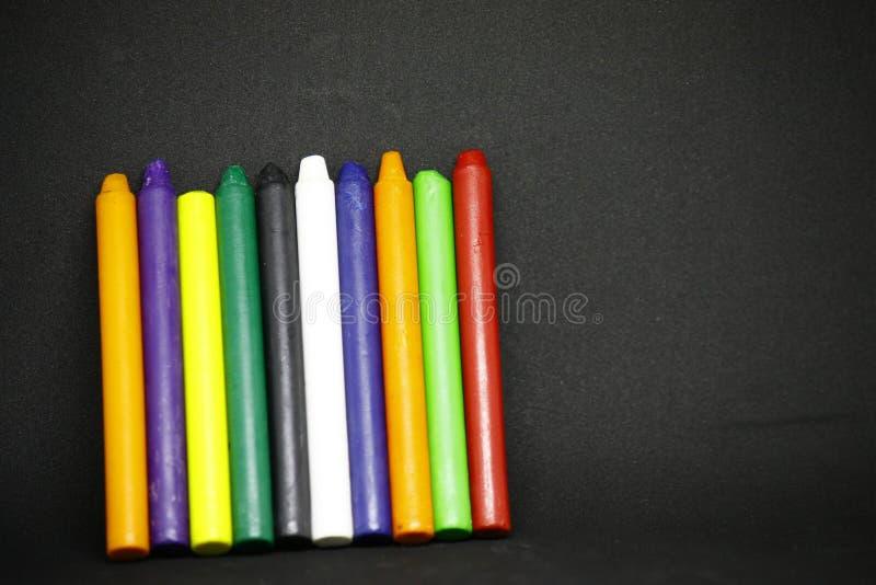 Tizas en una variedad de colores en fondo negro foto de archivo libre de regalías