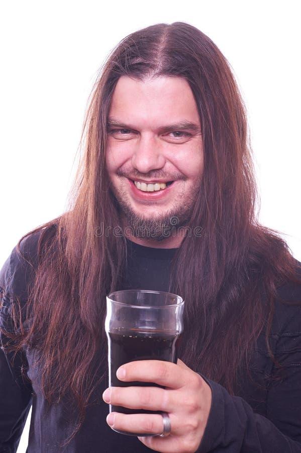 Tizio con capelli scorrenti che sorride e che tiene il vetro di birra fotografia stock libera da diritti