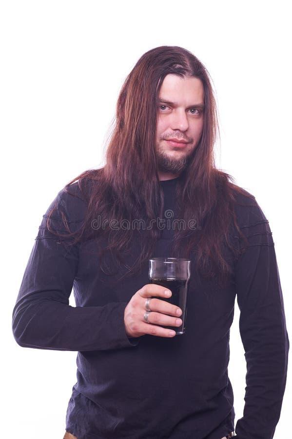 Tizio con il vetro di birra scorrente della tenuta dei capelli immagine stock libera da diritti