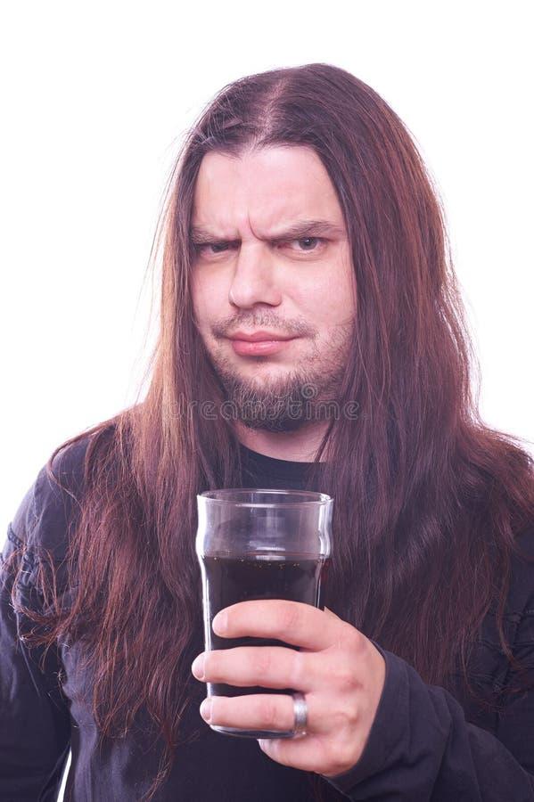 Tizio con il vetro di birra scorrente della tenuta dei capelli immagini stock