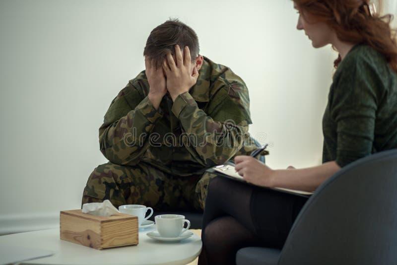 Tjäna som soldat dölja hans framsida i hans händer, medan tala till en psykiater under terapi arkivbild