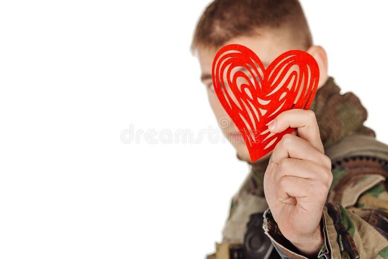 Tjäna som soldat det hållande hjärta formade valentinkortet och att le medan st arkivbild