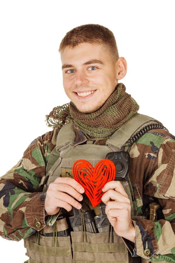Tjäna som soldat det hållande hjärta formade valentinkortet och att le medan st royaltyfri foto