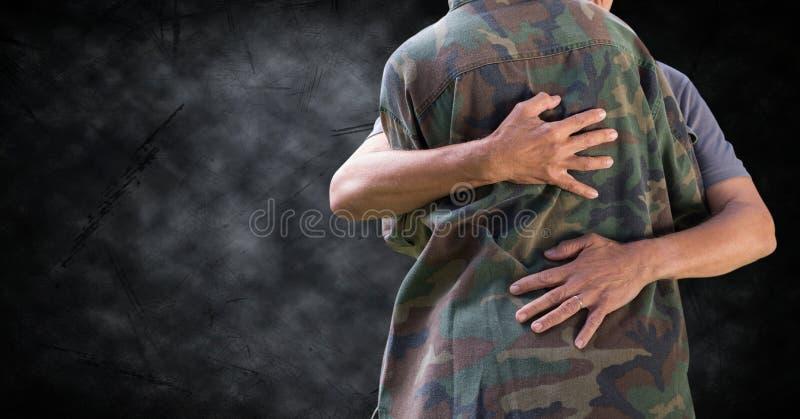 Tjäna som soldat krama det mitt- avsnittet mot svart grungebakgrund arkivfoton