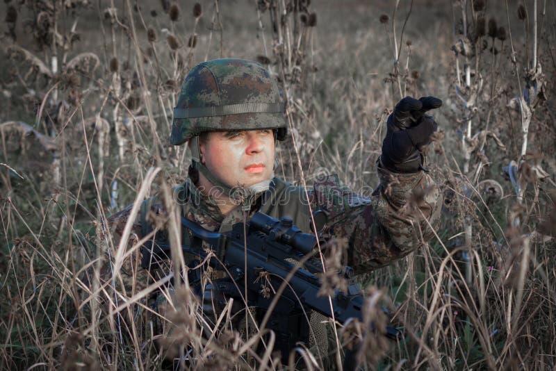 Tjäna som soldat med den militära hjälmen och vapnet som kamoufleras i handling arkivbild