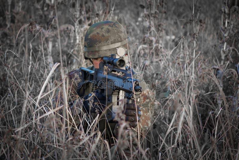 Tjäna som soldat med den militära hjälmen och vapnet som kamoufleras i handling - skjuta från bakhåll forsen arkivfoto