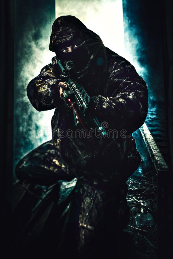 Tjäna som soldat rymma hans gevär med laser som vänds på arkivfoto
