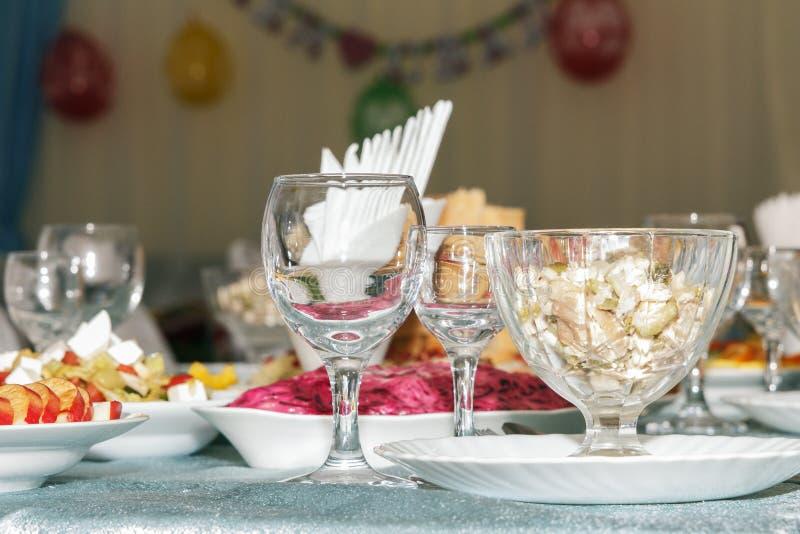 Tjänad som banketttabell med suddig bakgrund Tomma vinexponeringsglas, grönsaksallad och skivad frukt Slapp fokus royaltyfria foton