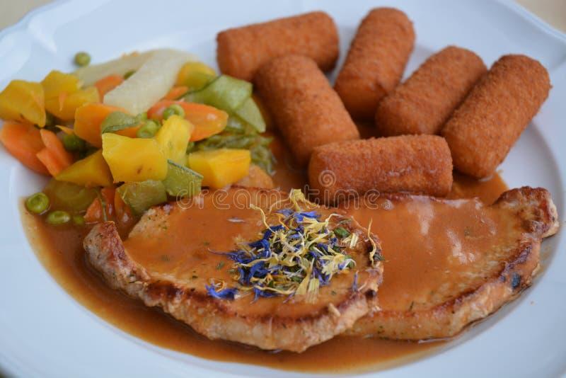 Tjänad som grisköttkotlett med Fried Potato Croquettes royaltyfria bilder