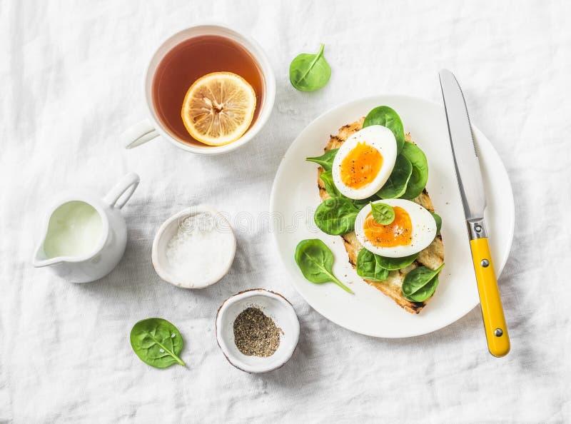 Tjänad som påskfrunchplatta - grillad brödsmörgås med spenat och kokat ägg och citronte på vit bakgrund royaltyfri bild