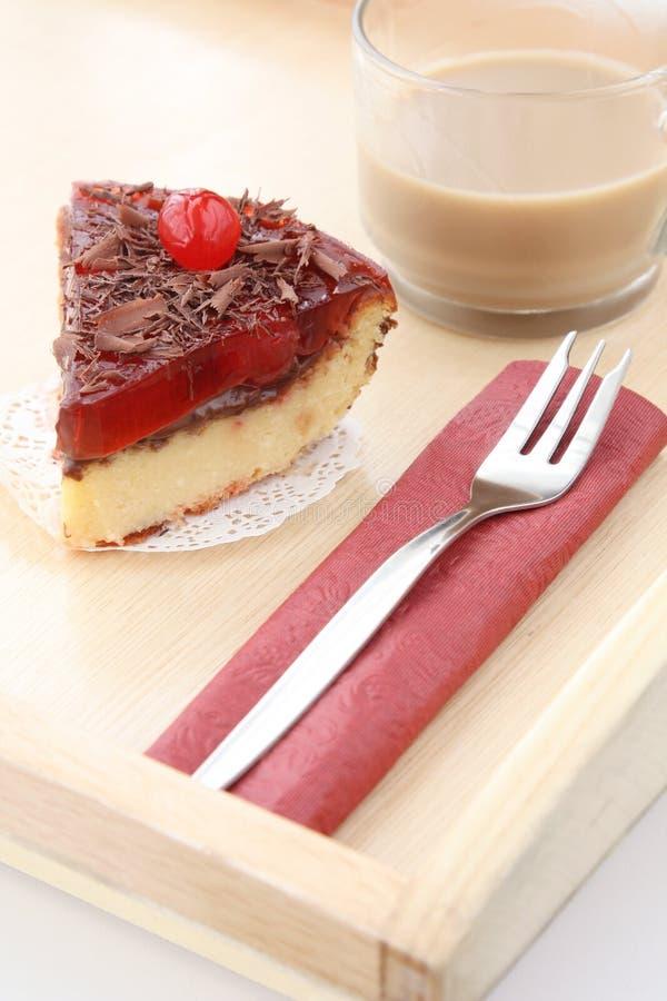 Tjänad som romantisk frukost: koppen kaffe med mjölkar och läcker körsbärsröd ostkaka royaltyfri bild
