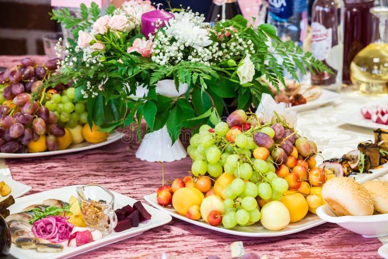 Tjänad som tabell på banketten Frukter, mellanmål, läckerheter och blommor i restaurangen Högtidlig händelse eller bröllop arkivfoto