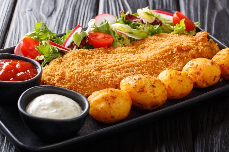 Tj?nad som torskfil?, i att panera med nya potatisar och salladn?rbild f?r ny gr?nsak p? en platta horisontal arkivfoto