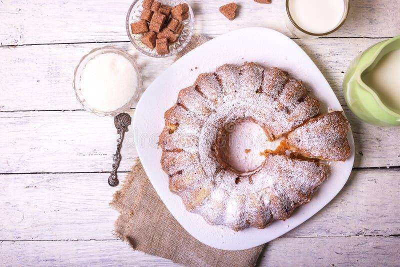 Tjänade som den frukt- hemlagade pajen för den söta rundan med hålet, på en vit maträtt på en trätabell med en kopp av mj royaltyfri bild