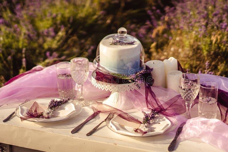 Tjänade som Festively tabellen med den lavendelbuketter och kakan royaltyfri fotografi