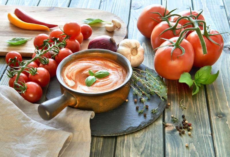 Tjänade som kräm- soppa för tomaten i en mörk keramisk bunke med kräm och b royaltyfria foton