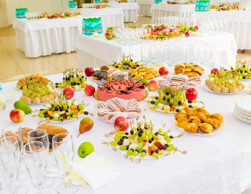 Tjänade som tabeller på banketten Efterrätter, frukt och bakelser på buffét Glasföremål- och mineralvattenflaskor Rosor i en till fotografering för bildbyråer