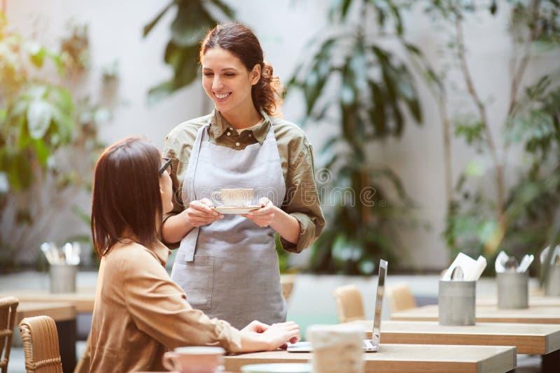 Tjänande som kaffe för attraktiv servitris till gästen royaltyfri bild