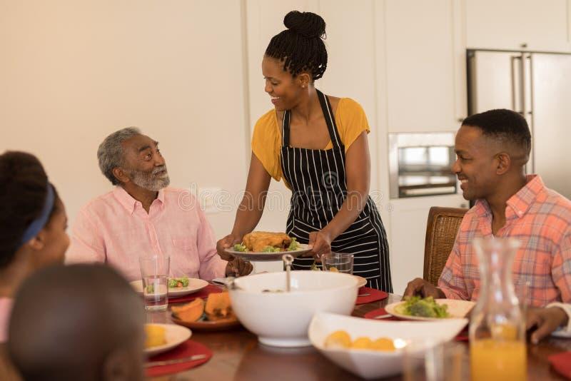Tjänande som mat för kvinna till hennes familj på den äta middag tabellen fotografering för bildbyråer