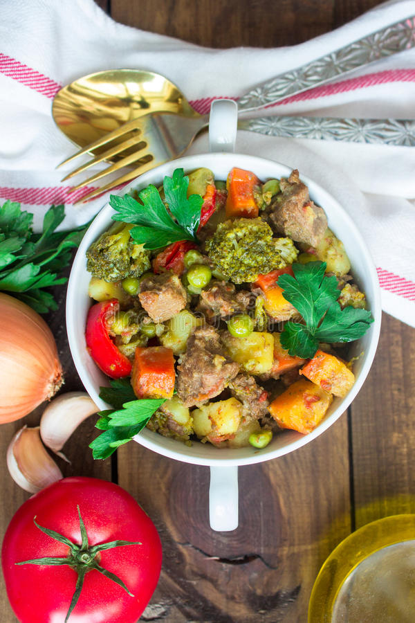 Tjänat som nötköttkött lät småkoka med grönsaker i keramisk kruka med ingredienser på träbakgrund royaltyfri bild